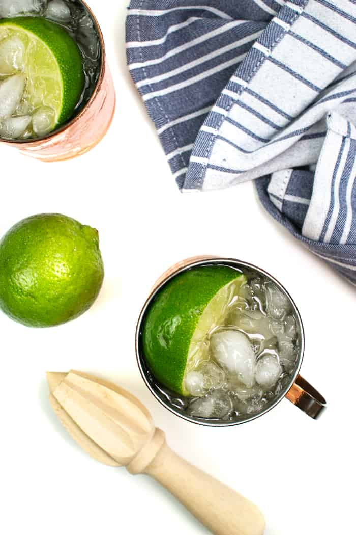 two kentucky moscow mules with limes and a citrus reamer