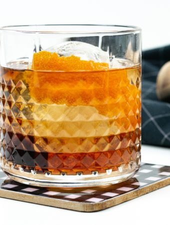 the best old-fashioned cocktail recipe in a patterned glass with a sphere ice cube on a black and white plaid coaster