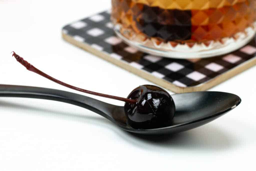 a close-up view of a cocktail cherry with stem on a black spoon next to an old-fashioned cocktail