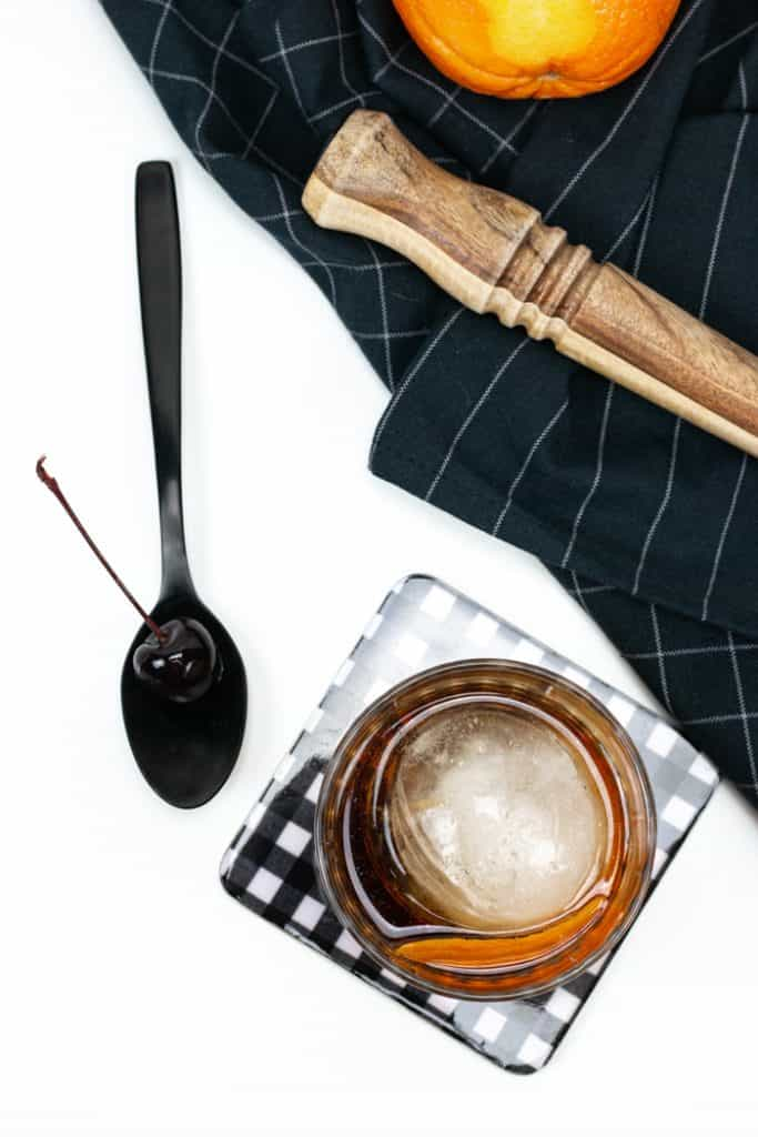 a wooden muddler and a cocktail cherry with an old-fashioned cocktail