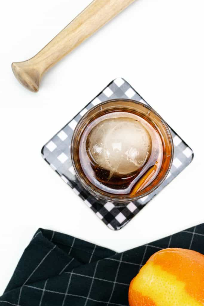 a wooden muddler and an orange with an old-fashioned cocktail on a black and white coaster