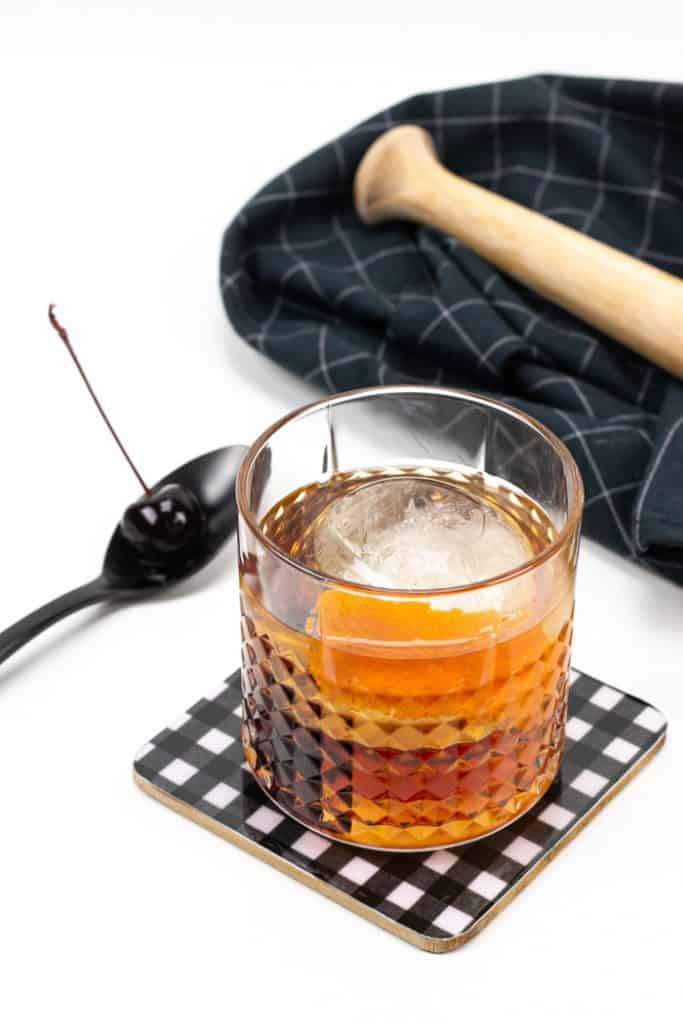 a cocktail cherry and an old-fashioned cocktail on a black and white plaid coaster