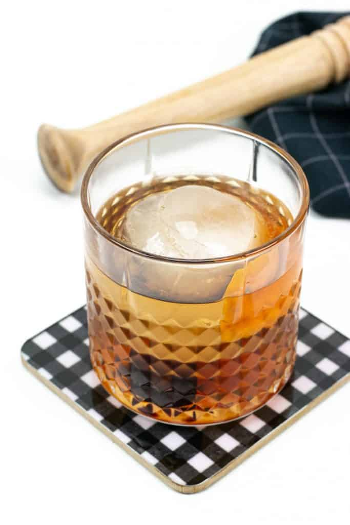 an old-fashioned cocktail with a black kitchen towel and a wooden muddler