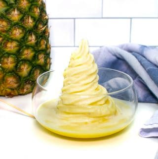 a dole whip made with rum next to a purple tea towel and cocktail umbrellas