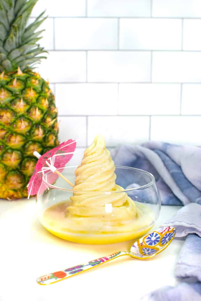 a pineapple with homemade dole whip with a pink cocktail umbrella