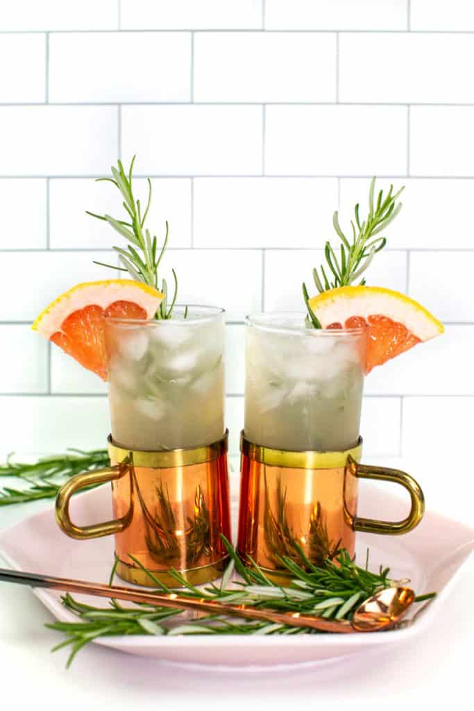 two grapefruit moscow mules in glass and copper mugs on a pink plate and garnished with rosemary