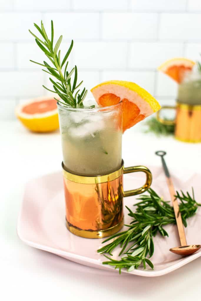 grapefruit mule cocktail on a pink hexagon plate with a copper spoon and rosemary
