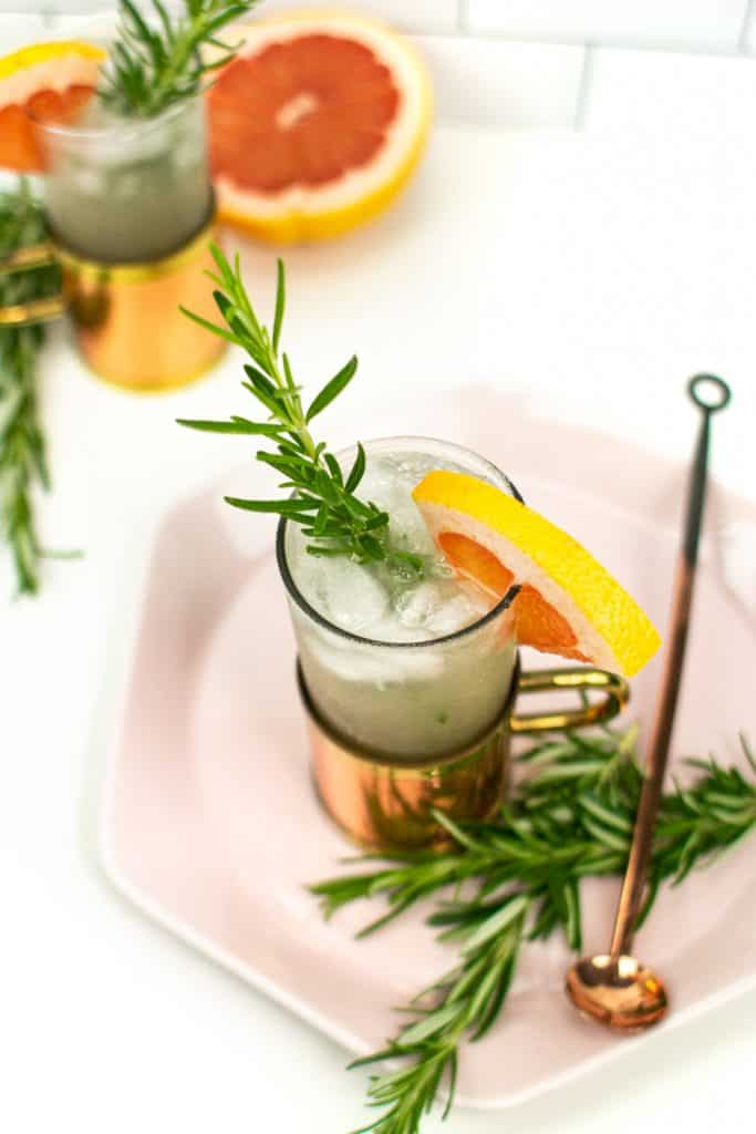 a grapefruit moscow mule on a pink hexagon plate with rosemary garnish, a copper cocktail spoon and half a grapefruit