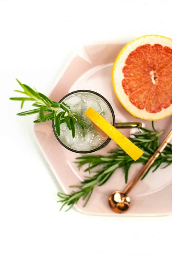 top view of a grapefruit moscow mule on a pink hexagon plate with rosemary garnish, a copper cocktail spoon and half a grapefruit