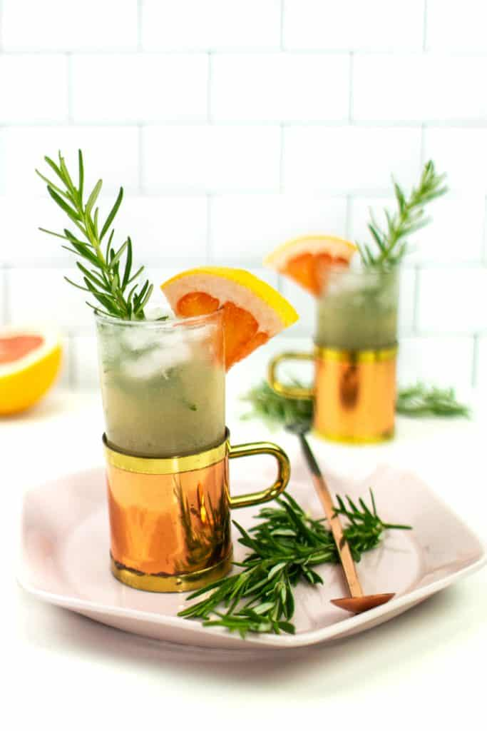 two grapefruit mule cocktails garnished with rosemary and a grapefruit wedge on a pink plate