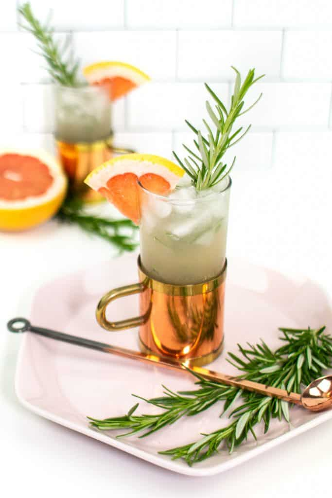 rosemary garnishes on a pink plate with a grapefruit mule cocktail