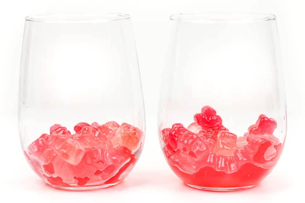 rosé gummy bears in two stemless wine glasses