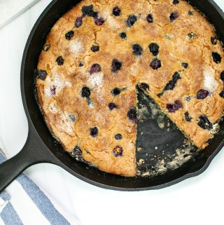 Skillet Blueberry Coffee Cake in.a cast iron skillet with a blue and white striped kitchen towel