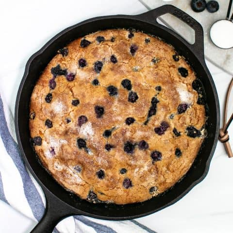 a pint of blueberries with a cast iron skillet with blueberry coffeecake
