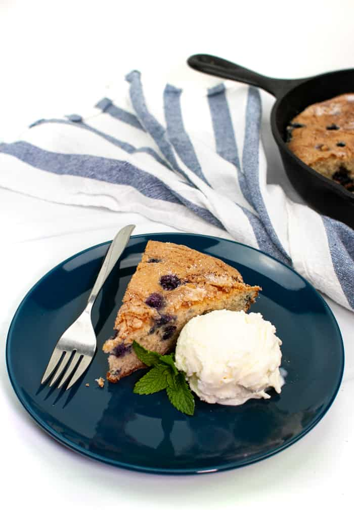 a slice of skillet blueberry coffee cake with a scoop of vanilla ice cream