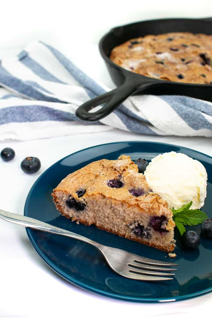 a slice of skillet blueberry coffee cake with a scoop of vanilla ice cream on a blue and white striped kitchen towel