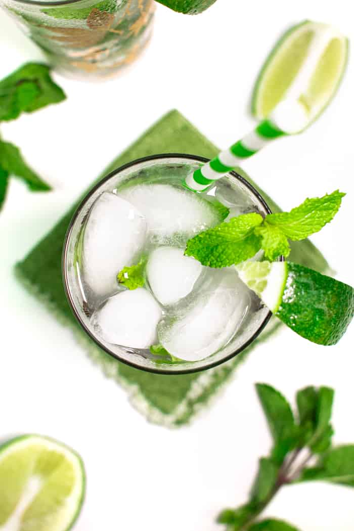 a classic mojito with mint leaves and lime wedges