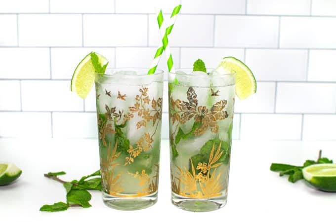two classic mojitos in glasses with gold designs on them