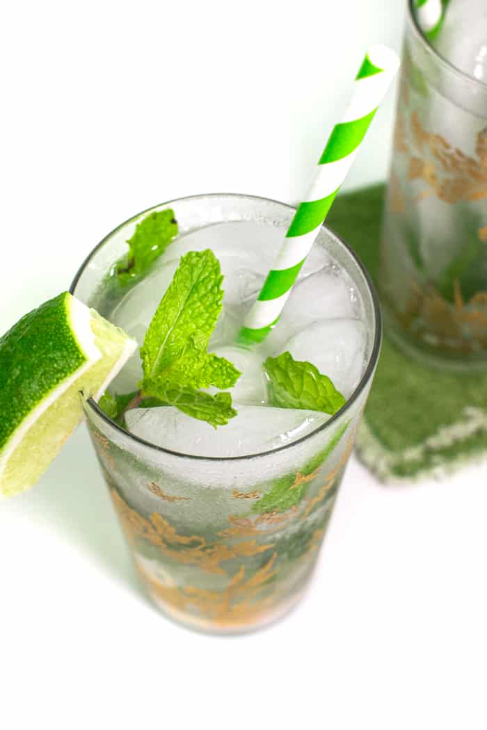 a classic mojito recipe garnished with a lime wedge and a sprig of fresh mint