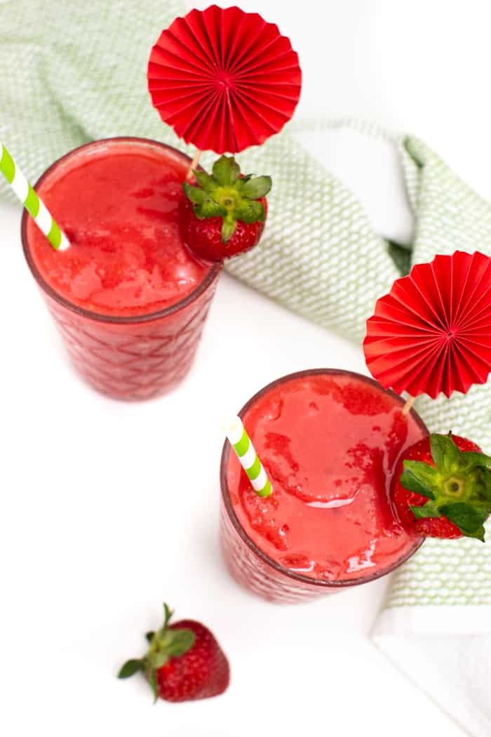 top down view of frozen strawberry daiquiris with a cocktail umbrella garnishes and strawberries