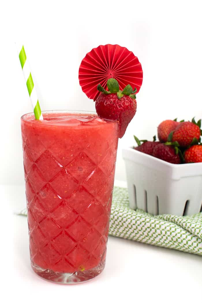 a pint of fresh strawberries next to a pair of frozen strawberry daiquiris