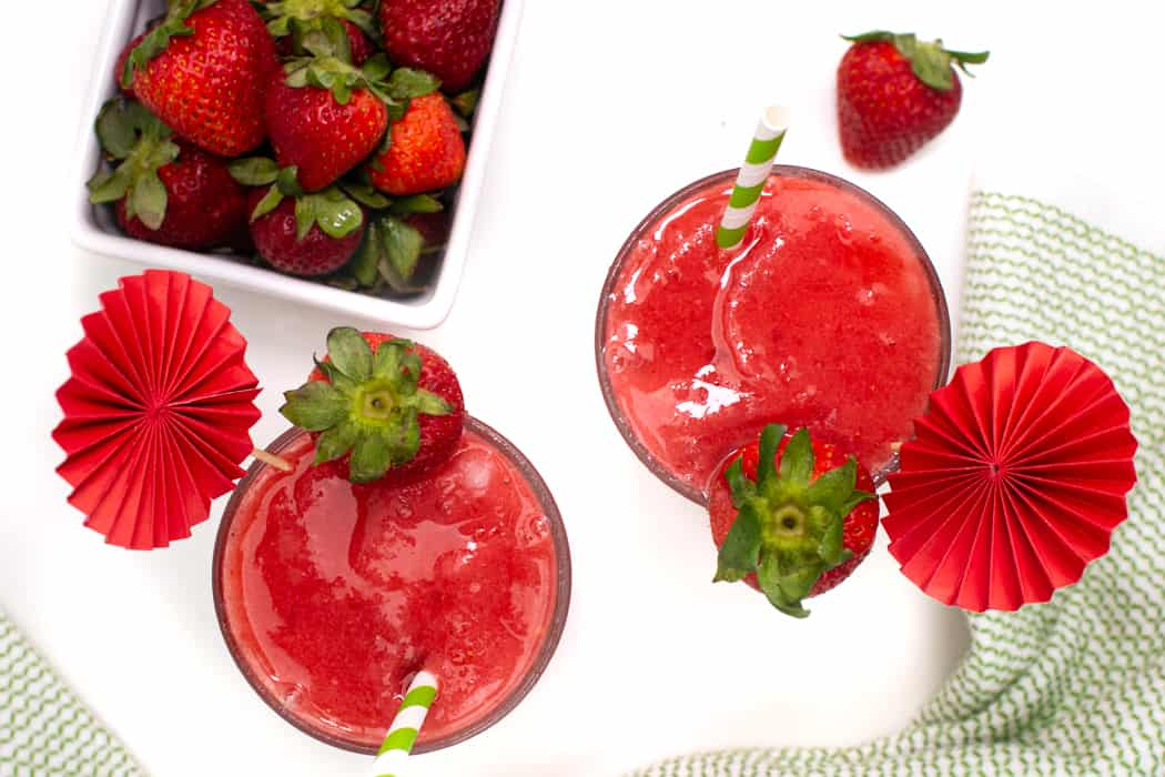 top view of a pint of fresh strawberries next to a pair of daiquiris