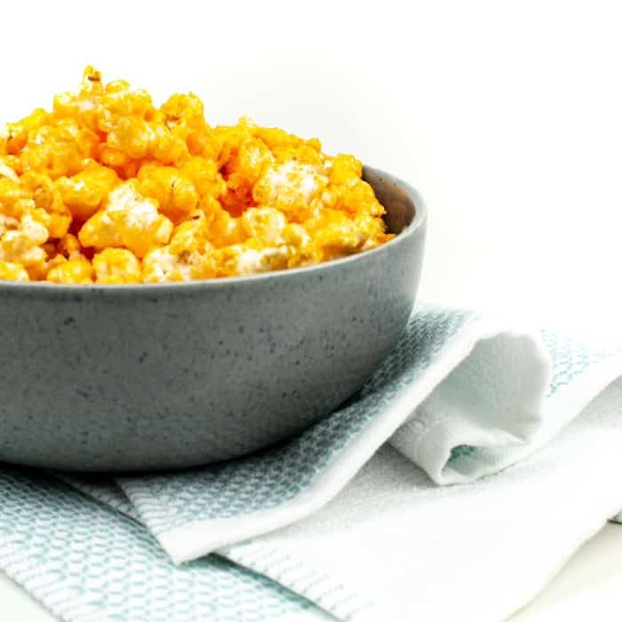 cheddar cheese popcorn in a gray bowl with a blue tea towel