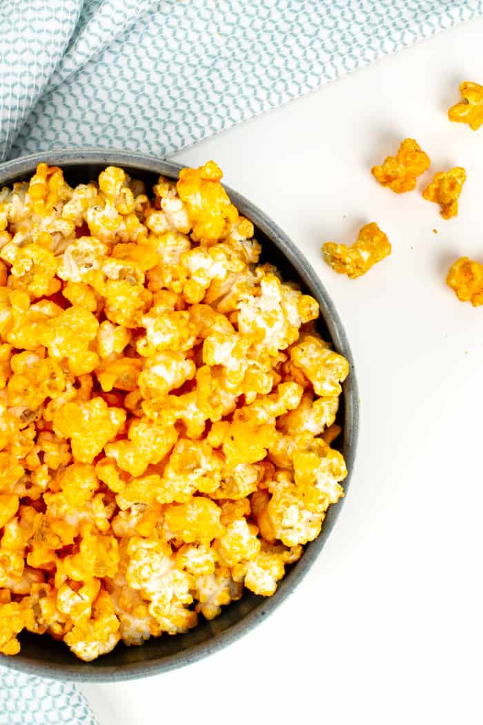 kernels of cheddar cheese popcorn spilling out of a bowl