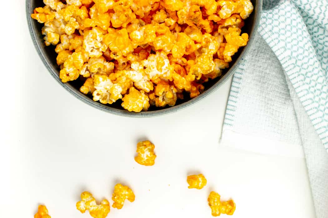 a bowl of cheddar cheese popcorn with kernels spilling out of the side of the bowl onto a white surface