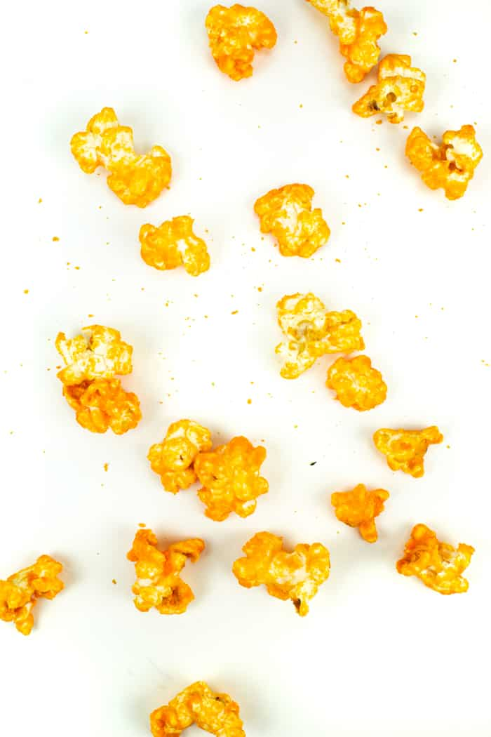 kernels of cheddar cheese popcorn on a white surface