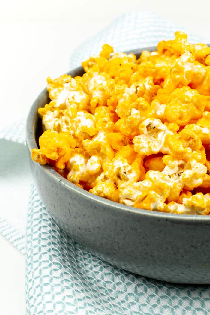 a heaping serving of cheese popcorn in a grey bowl