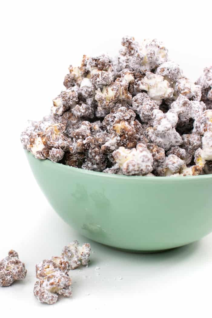 a mint green bowl filled with Puppy Chow Popcorn