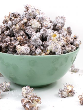 kernels of Puppy Chow Popcorn spilling out of a mint green bowl
