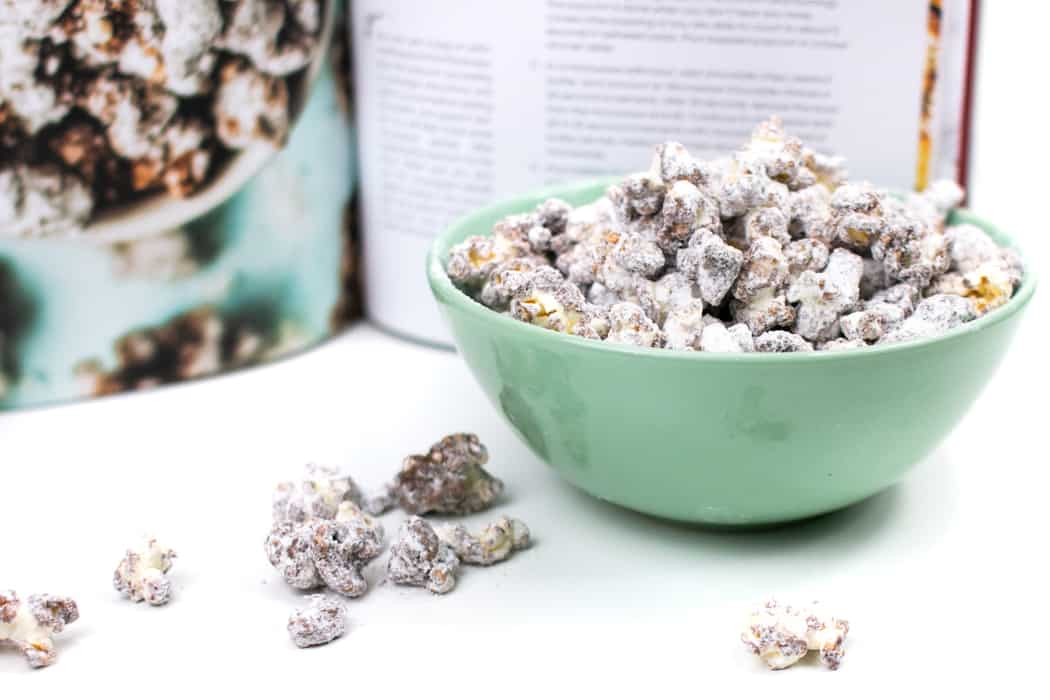 a green bowl filled with Puppy Chow Popcorn next to the Stunning Spreads cookbook open to the Puppy Chow Popcorn recipe