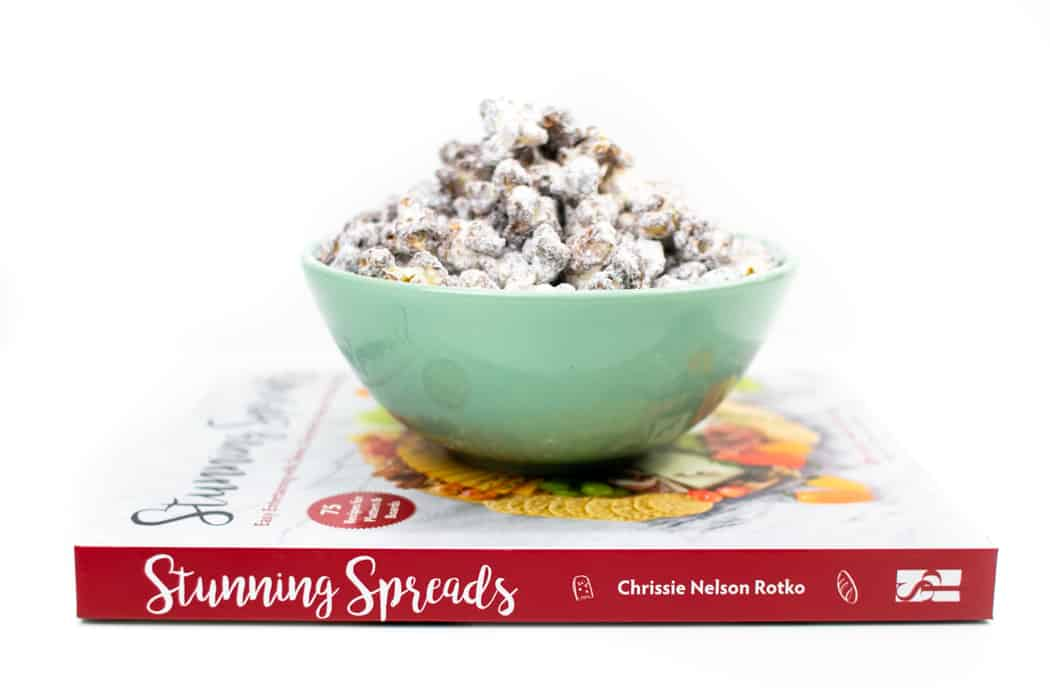 stunning spreads cookbook with a bowl of Puppy Chow Popcorn on top of it