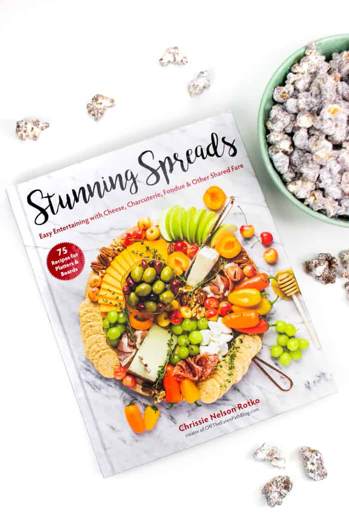 a copy of the stunning spread cookbook with puppy chow popcorn next to it