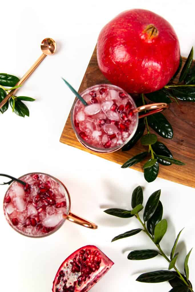 top view of christmas moscow mules with a pomegranate and holly on a white background