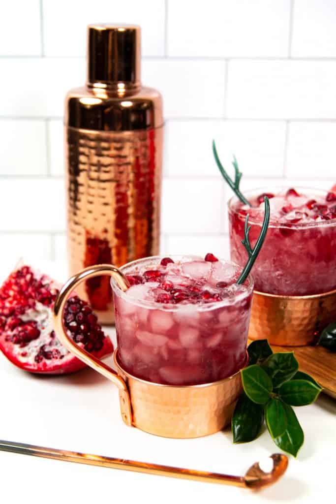 a copper cocktail shaker with pomegranate yule mules