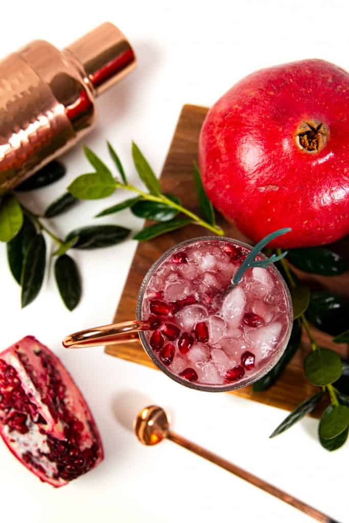 top view of a holiday moscow mule with a copper spoon and a wedge of pomegranate