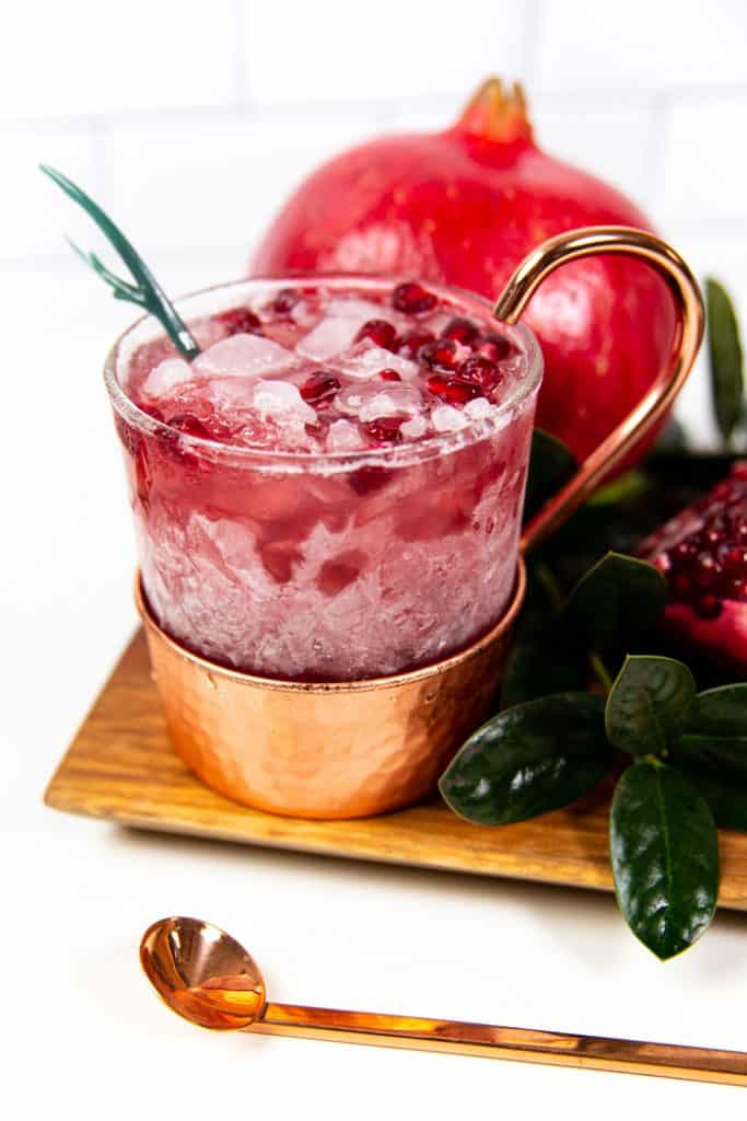 a pomegranate yule mule with a leafy garnish and pomegranate seeds on top