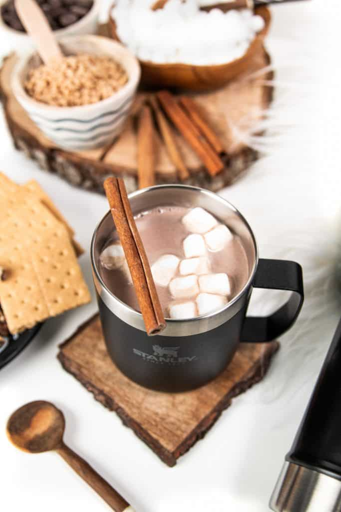 a stanley camp mug with hot chocolate and mini marshmallows on a wooden coaster