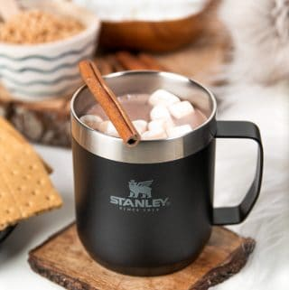 hot chocolate with marshmallows and a cinnamon stick in a stanley drinkware mug