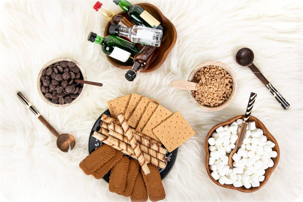 toppings for a hot chocolate party arranged in bowls on a sheepskin rug