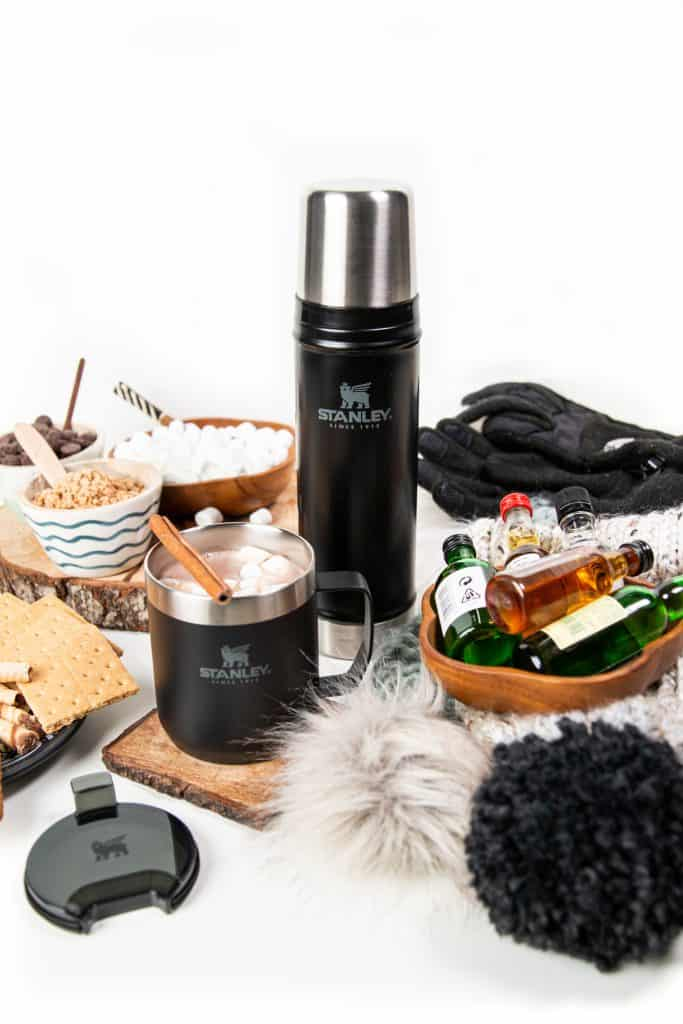 stanley drinkware and hot chocolate toppings spread out for a hot chocolate party