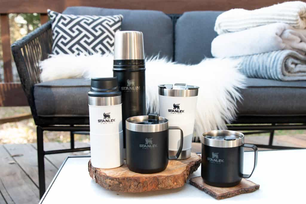 black and white stanley brand drinkware on a patio table outside near a couch with a sheepskin and stack of blankets