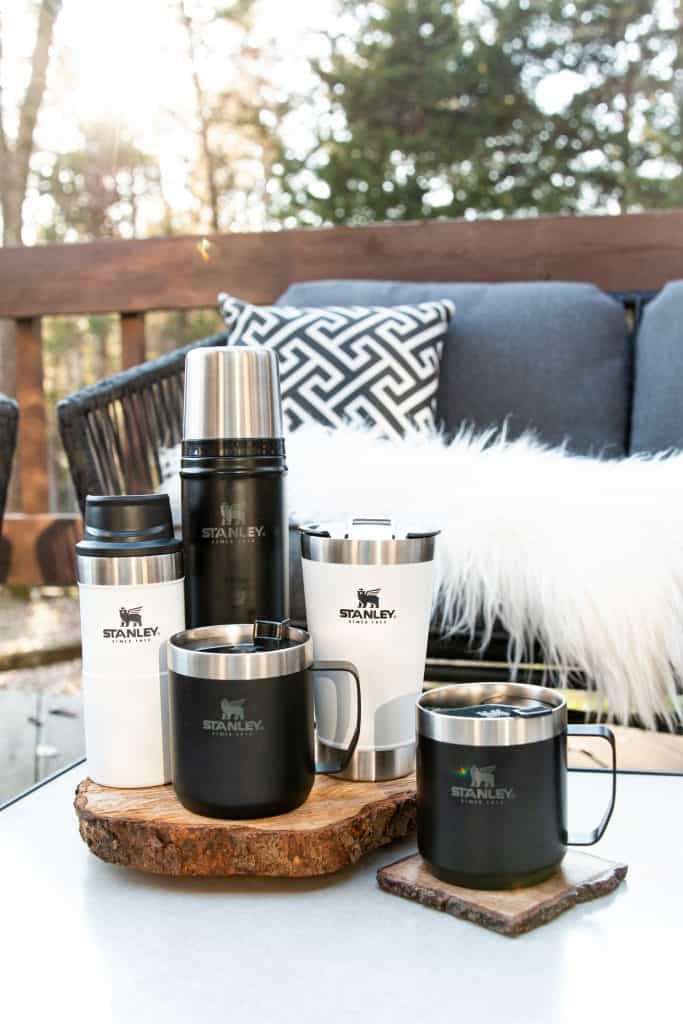 black and white stanley brand drinkware on a patio table outside