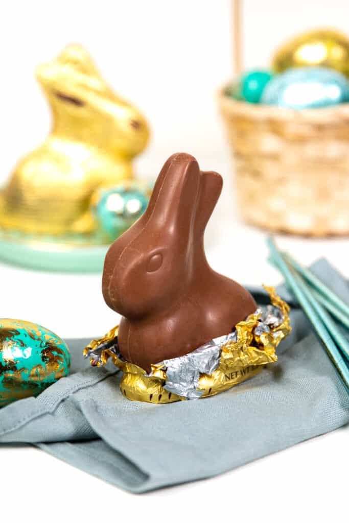 an unwrapped chocolate bunny resting on a blue napkin.