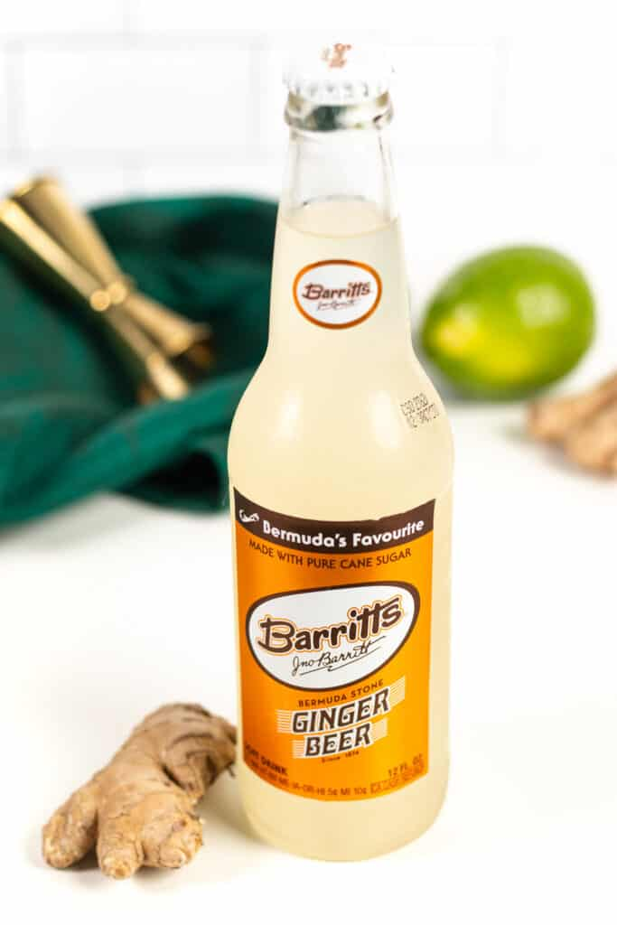 a bottle of barritt's ginger beer on a white countertop with a piece of ginger root, a lime, a green tea towel and a cocktail jigger.