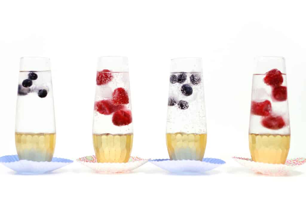 four stemless champagne glasses with gold details containing sparkling water and berry ice cubes