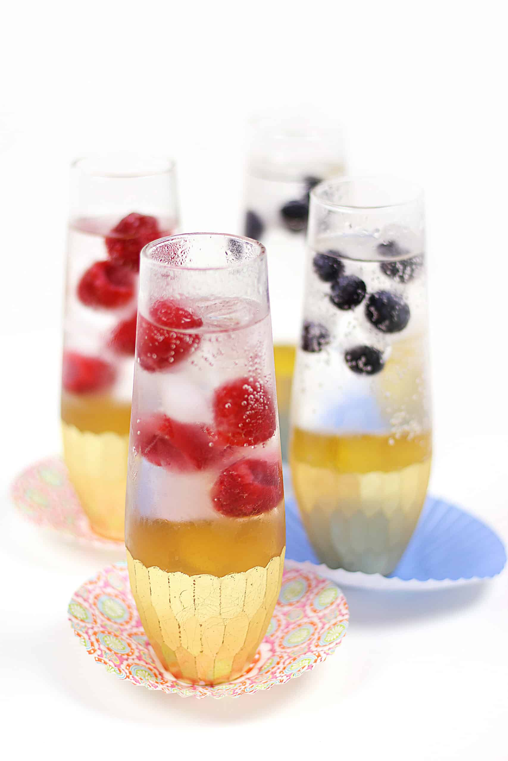 four sparkling cocktails with raspberry and blueberry ice cubes